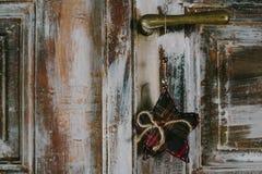 Декоративная смертная казнь через повешение звезды рождества на старой ручке двери Стоковые Фотографии RF