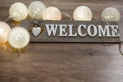 Декоративное гостеприимсво текста с сердцем и светами на деревянном столе Стоковое фото RF