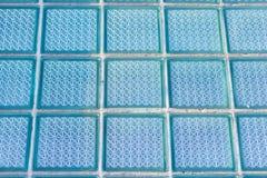 Декоративное и лоснистое окно стеклянного блока в сини как текстура или для предпосылки предпосылка геометрическая Стоковое Изображение RF