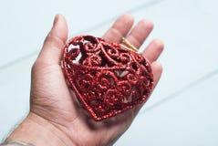 Декоративное красное сердце на ладони, Стоковое Фото