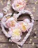 Декоративное сердце и розовые пионы цветут на постаретом деревянном backgr Стоковые Фотографии RF