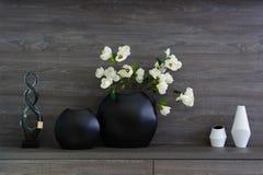 Декоративные вазы и цветки на темной деревянной полке Стоковые Фото