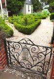 """Декоративные ворота водят к белому гравию и детальному благоустраивать на резиденции """" стоковое изображение"""