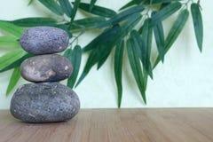 Декоративные камешки штабелированные в моде жизни Дзэн на бамбуковой деревянной доске на зеленом цвете и предпосылке листвы Стоковое фото RF