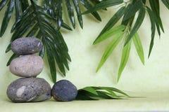 Декоративные камешки штабелированные в моде жизни Дзэн на зеленой предпосылке Стоковое Фото