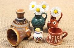Декоративные керамические вазы и белые маргаритки на холсте джута Стоковое фото RF