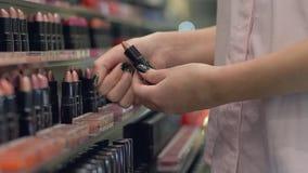 Декоративные косметики женщин, модная женщина выбирают губную помаду для яркого макияжа и прикладывают косметики испытывая в нали сток-видео
