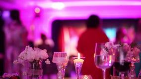 Декоративные свечи на обеденном столе, стеклах и свечах рождества на таблице, party на заднем плане, ресторан акции видеоматериалы
