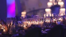 Декоративные свечи на обеденном столе, стеклах и свечах на таблице, белом стекле рождества candleswith воска акции видеоматериалы