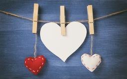 Декоративные сердца вися на веревочке против голубой деревянной стены Стоковые Фото