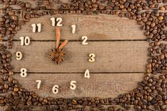 Декоративные часы с деревянными цифрами и стрелки сделанные из ручек циннамона, показывающ 1 час, на деревянной предпосылке и рам стоковые изображения