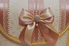 Декоративный комод свадьбы для денег, обитый с тканью Cream сатинировка, шарики и декоративный шкентель текстура Стоковая Фотография