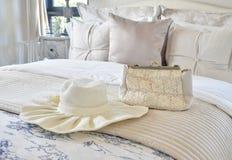 Декоративный комплект с винтажной сумкой и шляпа на кровати в роскошной спальне Стоковые Фото