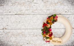 Декоративный орнамент двери помечает буквами дом слова с высушенными цветками Стоковые Изображения