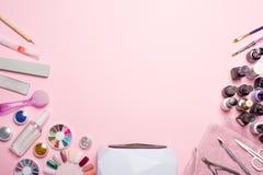 Делайте маникюр - инструменты для создания, блески геля, все для обработки ногтей, концепции красоты, заботы Пинк Backgr знамени  стоковая фотография