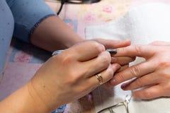 делать женщину manicure процесс создания конца-вверх рук маникюра позаботьте ноготь ногтя хлопка извлекая политуру пробирки стоковая фотография rf