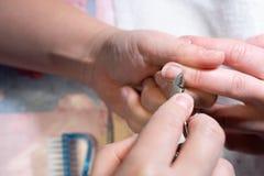 делать женщину manicure процесс создания конца-вверх рук маникюра позаботьте ноготь ногтя хлопка извлекая политуру пробирки стоковое фото