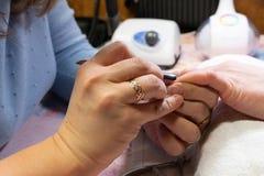 делать женщину manicure процесс создания конца-вверх рук маникюра позаботьте ноготь ногтя хлопка извлекая политуру пробирки стоковое изображение rf