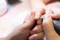 делать женщину manicure процесс создания конца-вверх рук маникюра позаботьте ноготь ногтя хлопка извлекая политуру пробирки стоковые фото