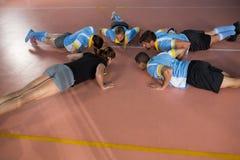 Делать команды волейбола нажим-поднимает с тренером Стоковые Изображения