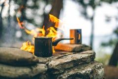 Делать кофе в cezve на камине располагаясь лагерем или пеший туризм кофе на лагерном костере стоковая фотография rf