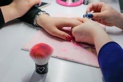 Делать краска ногтя, съемка крупного плана женщины в салоне ногтя получая маникюр beautician стоковая фотография