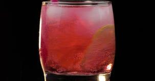 Делать освежая красный коктейль напитка в стекле с льдом, и известкой видеоматериал