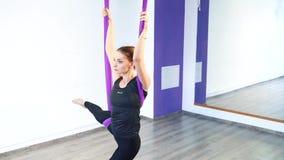делать протягивающ детенышей женщины Фитнес, протягивать, баланс, тренировка и здоровый образ жизни Женщина используя гамак видеоматериал