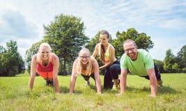 Делать семьи нажим-поднимает в природе под наведением тренером фитнеса стоковое изображение rf