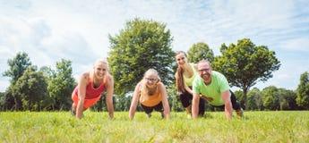Делать семьи нажим-поднимает в природе под наведением coac фитнеса стоковые изображения rf