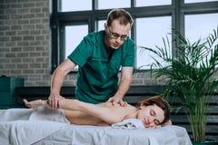 Делать терапевта массажа massotherapy молодой женщины Красивая расслабленная сторона молодой женщины с каштановыми волосами стоковые фотографии rf