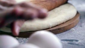 Делать тесто женскими руками на предпосылке деревянного стола сток-видео