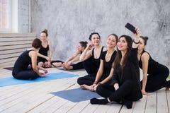 Делать selfie Группа в составе девушки в классе фитнеса на проломе смотря сотовый телефон, счастливый и усмехаясь, показывает сме стоковые изображения