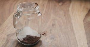 Делающ какао выпить в стеклянном опарнике с ручкой на деревянной таблице, добавляя сахар Стоковые Фото