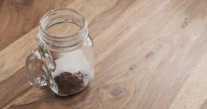 Делающ какао выпить в стеклянном опарнике с ручкой на деревянной таблице, добавляя сахар Стоковое фото RF