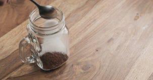 Делающ какао выпить в стеклянном опарнике с ручкой на деревянной таблице, добавляя сахар Стоковая Фотография RF