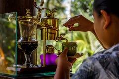 Делающ легендарный кофе, Kopi Luwak, в годе сбора винограда переливает через сифон bali Индонесия стоковое фото