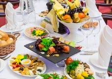 Деликатесы, закуски и плод на праздничной таблице в ресторане Торжество catering салаты сока виноградин плодоовощ фокуса корзины  стоковое изображение
