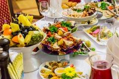 Деликатесы, закуски и плод на праздничной таблице в ресторане Торжество catering салаты сока виноградин плодоовощ фокуса корзины  стоковое фото rf