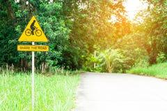 Делите дорожный знак с велосипедистом знак катания велосипеда в мёде Стоковые Изображения