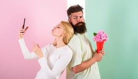 Делить счастливое selfie Женщина захватывая счастливый парня момента приносит цветки букета Пары в датировка букета влюбленности стоковое фото rf