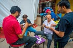 Дели, Индия - 25-ое сентября 2017: Группа в составе карточки друзей играя в улицах Paharganj Дели с мусульманскими покупателями Стоковая Фотография RF