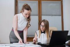 2 делового партнера женщин смотрят на финансовых отчетах, статистик и документах Стоковое Изображение RF