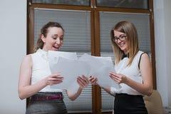 2 делового партнера женщин смотрят на финансовых отчетах, статистик и документах Стоковые Изображения RF