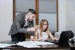 2 делового партнера обсуждают планы или идеи сидя на столе и работая на компьтер-книжке Стоковые Изображения RF