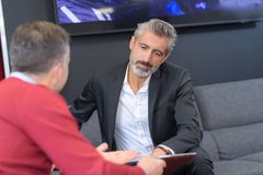 2 делового партнера сидя на софе и говорить Стоковое Фото