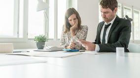 2 делового партнера суммируя номера на recei распечатки Стоковые Фото