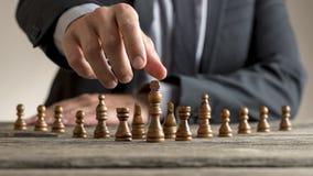 Деловой костюм бизнесмена нося достигая темную шахматную фигуру короля Стоковое Изображение