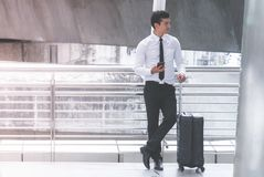 Деловой путешественник с багажом использует его мобильный телефон стоковая фотография