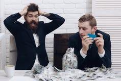 Деловые партнеры, бизнесмены на встрече в офисе Бородатый сотрясенный босс и коллега с карточкой наличных денег и пластмассы Стоковая Фотография